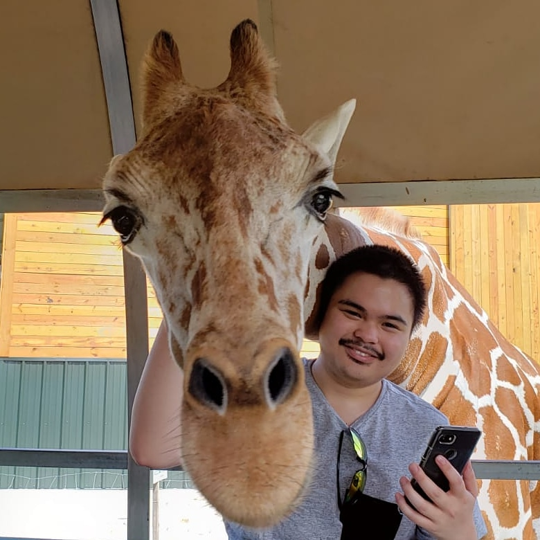 The website creator next to a giraffe